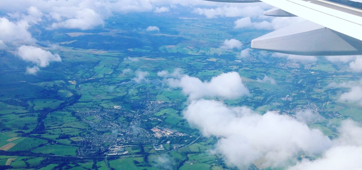 Image of the wing of a plane and a country seen from the air.